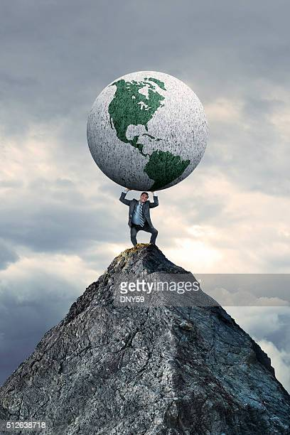 Businessman Standing On Mountain Top Holding A Globe