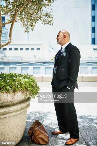 Businessman standing on office building deck waiting