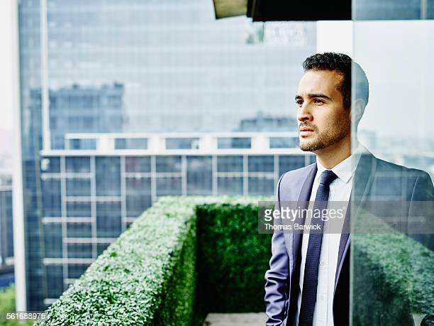 Businessman standing on office terrace looking out