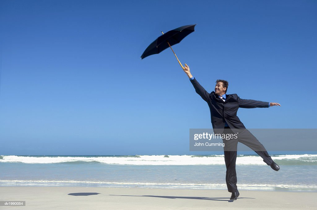 Businessman Standing on One Leg and Holding an Umbrella, on a Beach : Stock Photo