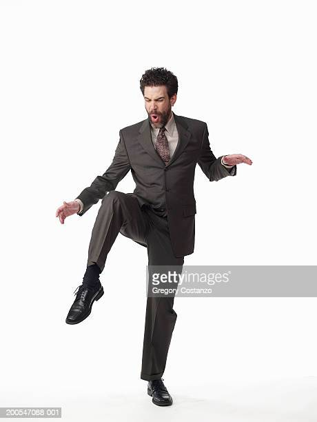 businessman standing on one leg, on white background, portrait - standing on one leg stock pictures, royalty-free photos & images