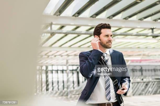 Businessman standing on parking level making a call using earphones