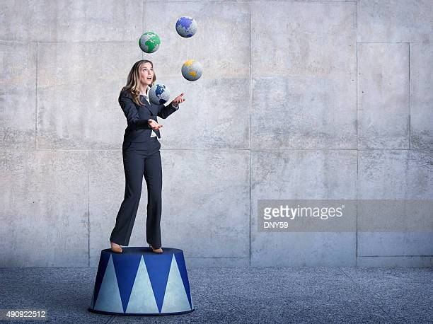 Businessman Standing On Pedestal Juggling Several Globes