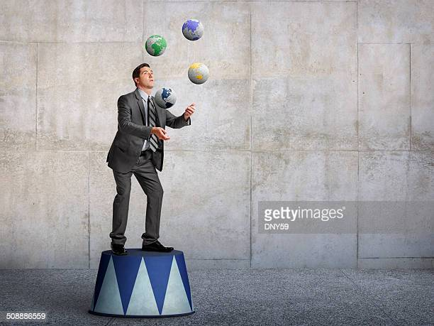 Businessman standing on pedestal juggling various globes of earth