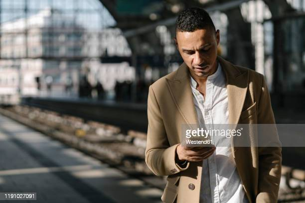 businessman standing on platform of train station alexanderplatz using smartphone, berlin, germany - menswear stock pictures, royalty-free photos & images