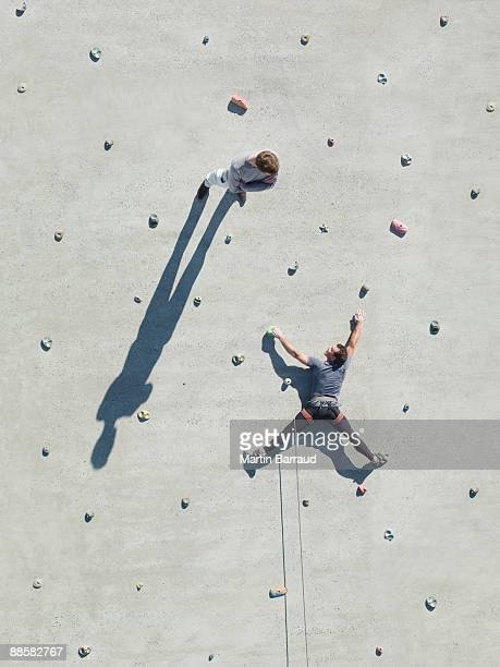 Businessman standing on rock climbing wall