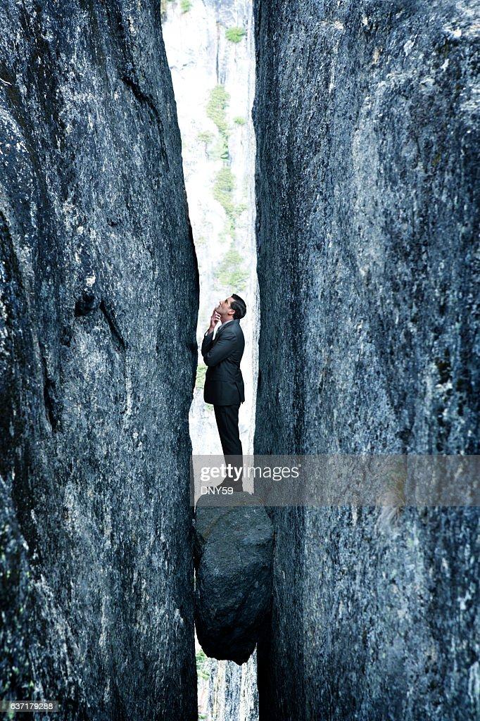 Businessman Standing On Rock Stuck In Deep Crevasse : Stock Photo