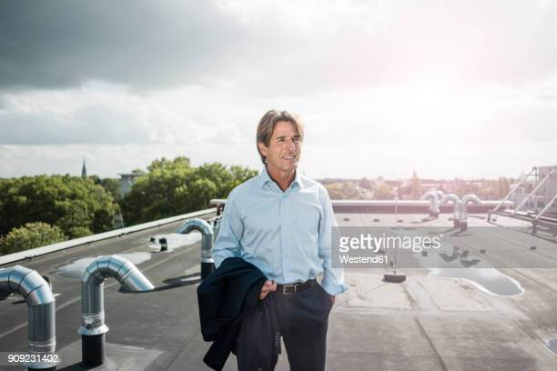 businessman standing on roof in the city - un solo hombre fotografías e imágenes de stock