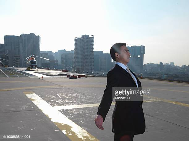 Businessman standing on runway with arms out, looking away, side view