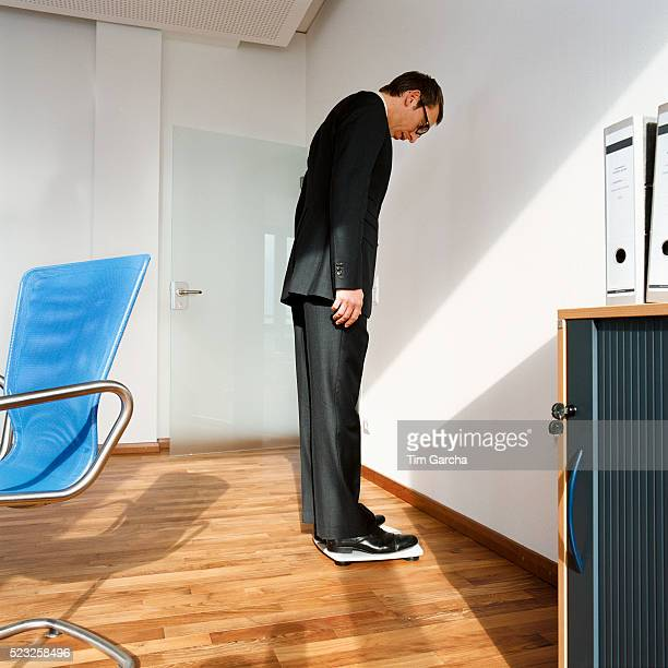 Businessman Standing on Scale in Office