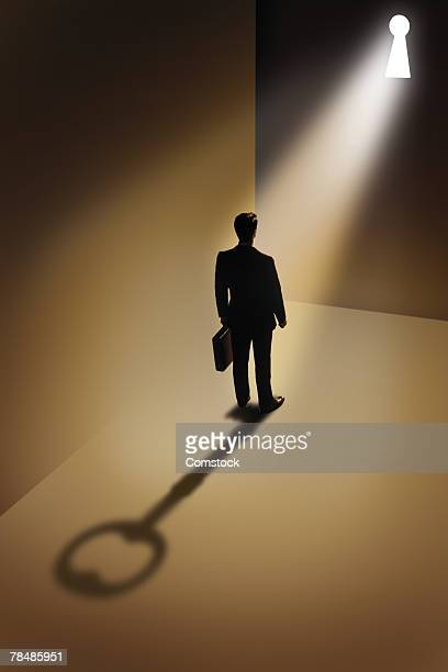 Businessman standing on shadow of key with keyhole