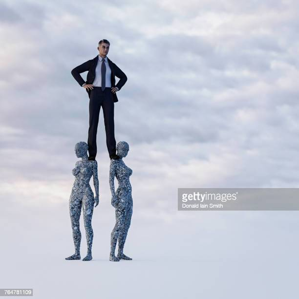 Businessman standing on shoulders of stone women