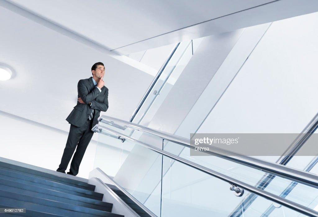 Businessman Standing On Stair Landing Looks Up Toward Next Flight Of