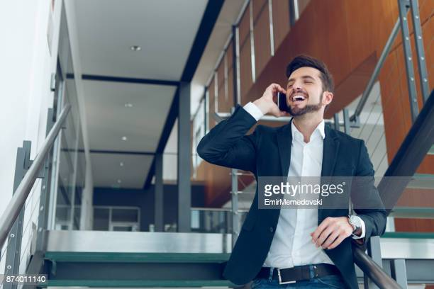 businessman standing on staircase and talking on mobile phone. - emir memedovski stock pictures, royalty-free photos & images