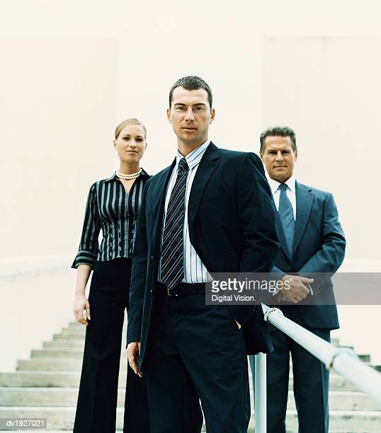 Businessman Standing on Steps in Front of Two Other Business Executives