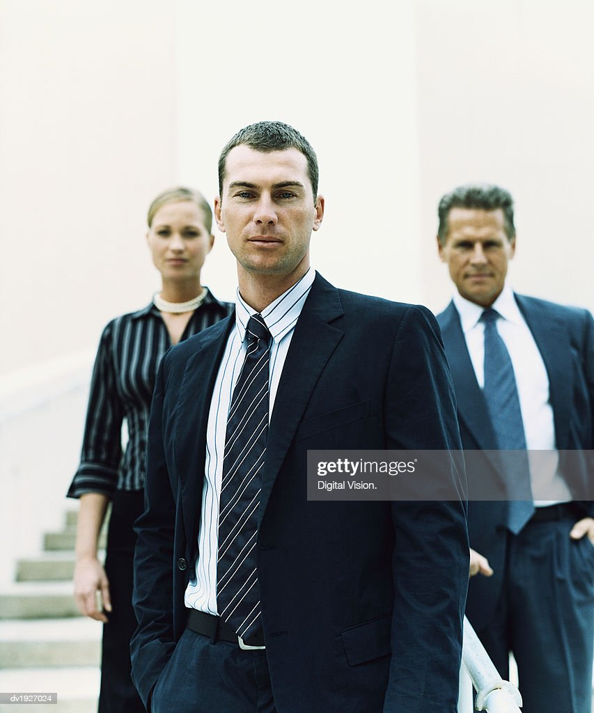Businessman Standing on Steps in Front of Two Other Business Executives : Stock Photo