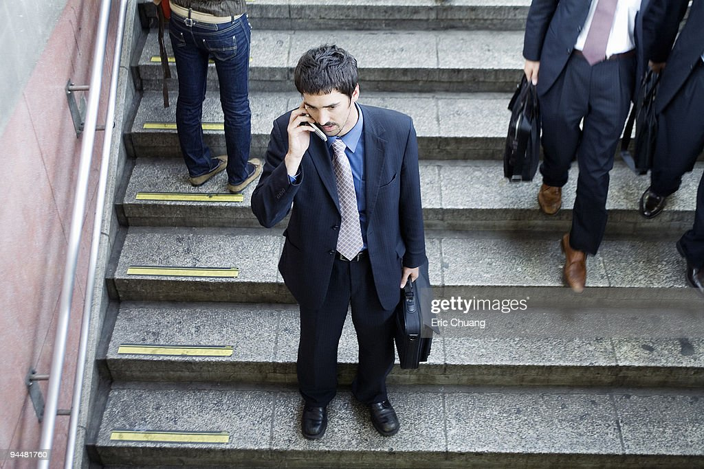 Businessman standing on steps talking on cell phone : Stock Photo