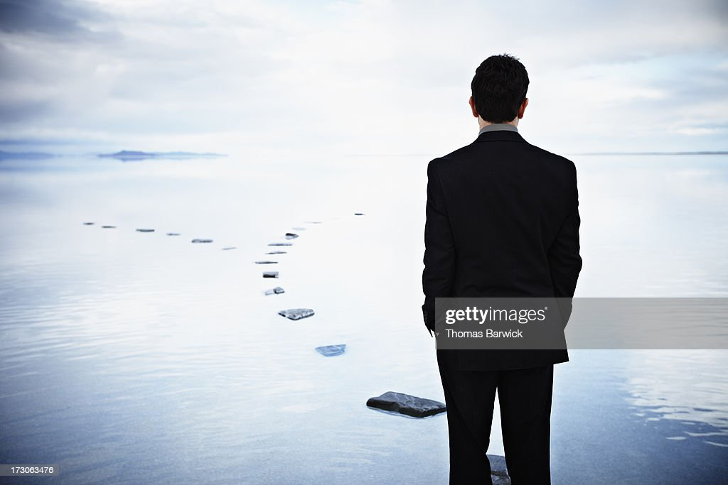 Businessman standing on stone pathway in water : Stock Photo