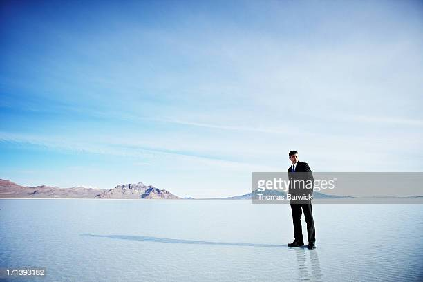 Businessman standing on surface of lake