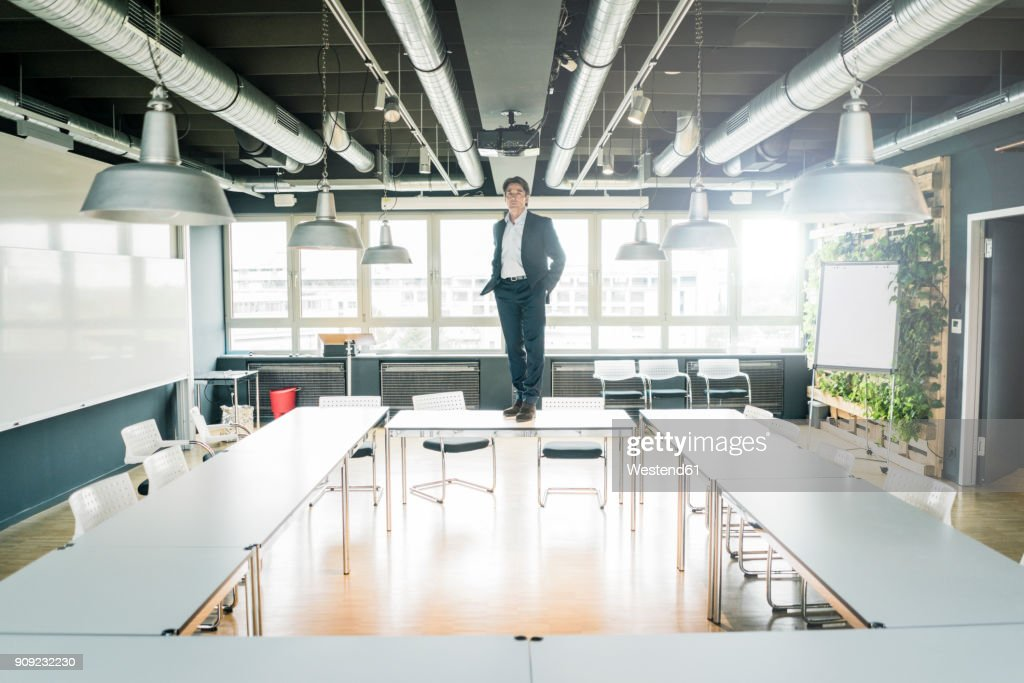 Businessman Standing On Table In Conference Room Stock Photo Getty - Standing conference room table