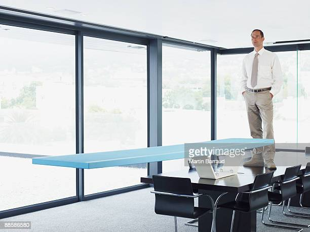 Businessman standing on table with diving board
