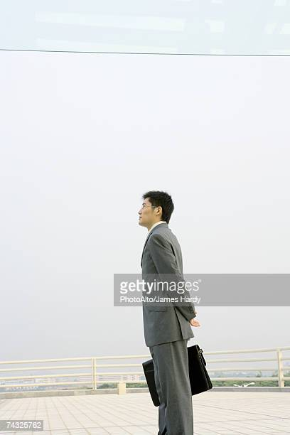 Businessman standing on terrace, looking toward distance