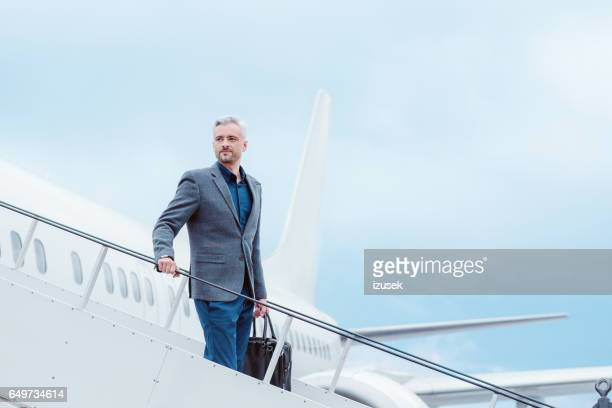 Businessman standing on the aircraft passenger stairs