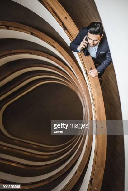 電話で話している、廊下に立っているビジネスマン