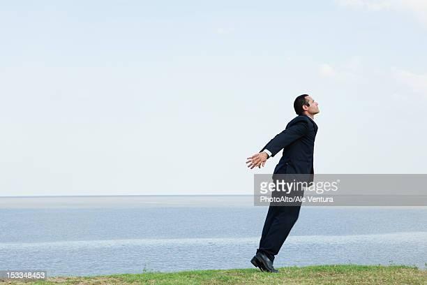 Businessman standing on tiptoe by sea, taking deep breath