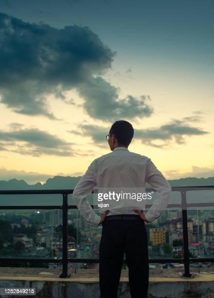 geschäftsmann steht auf einem gebäude, das sonnenuntergang aussieht - lateinamerika stock-fotos und bilder