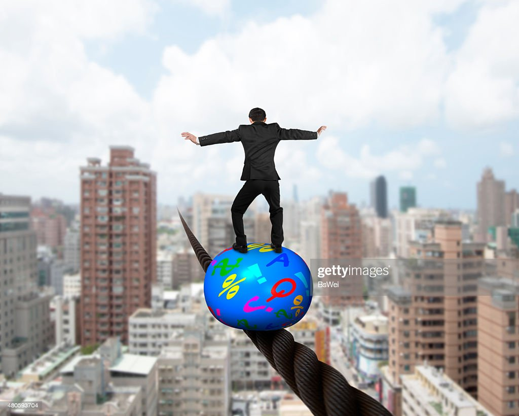 Businessman standing on top of ball balancing on wire : Stock Photo