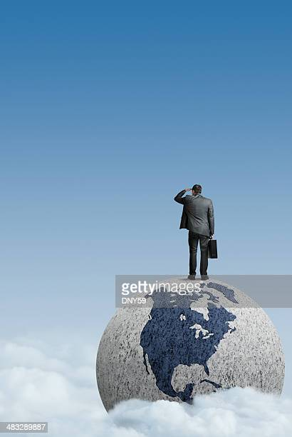Businessman standing on top of globe looking into distance