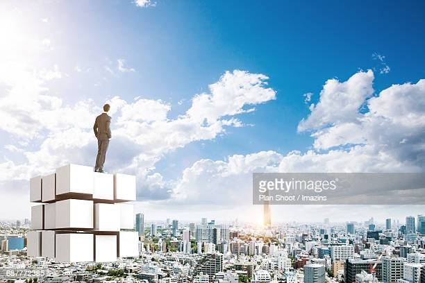 A businessman standing on top of puzzle cube and a cityview