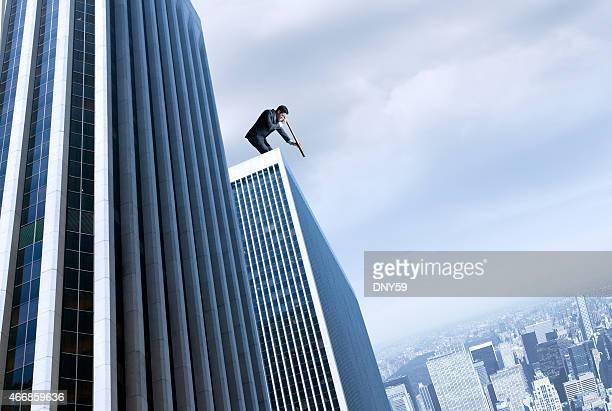 Geschäftsmann, stehen auf Wolkenkratzer, die durch ein spyglass