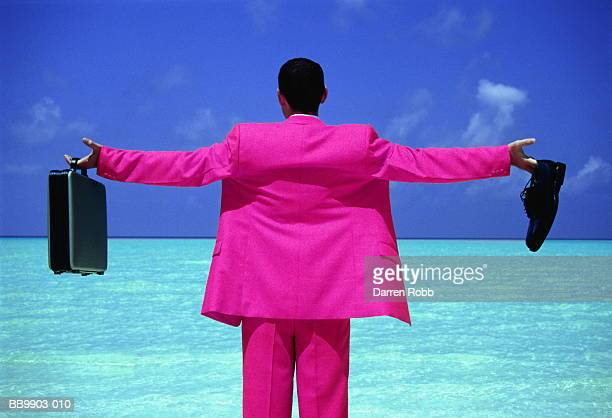 Businessman standing on tropical beach, arms outstretched, rear view