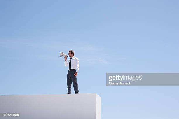 businessman standing on wall shouting through megaphone  - blue balls pics stock pictures, royalty-free photos & images