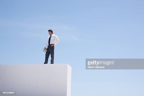businessman standing on wall with megaphone  - blue balls pics stock pictures, royalty-free photos & images