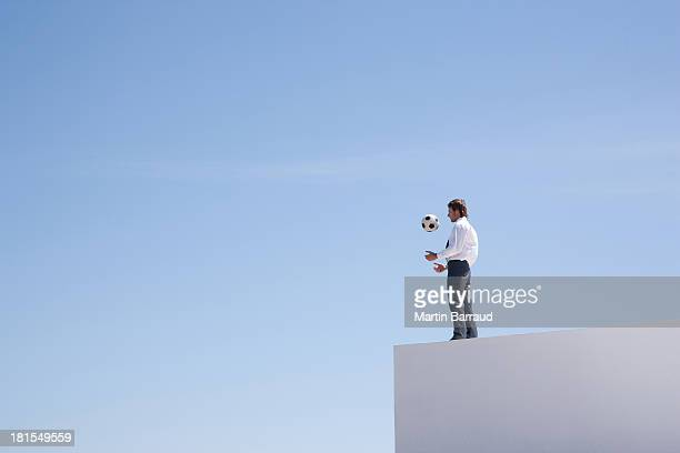 businessman standing on wall with soccer ball outdoors - blue balls pics stock pictures, royalty-free photos & images