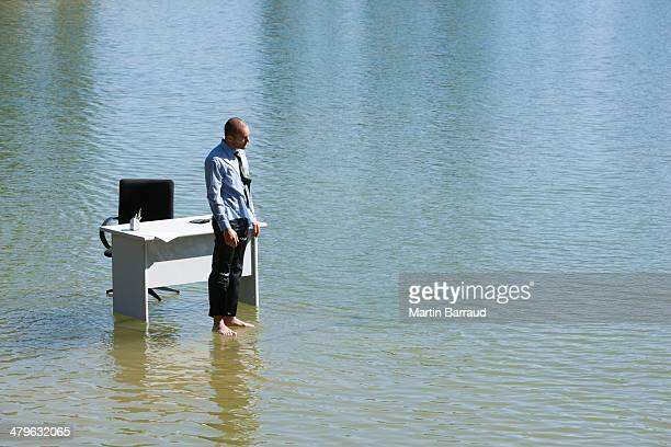 Businessman standing on water with desk and chair