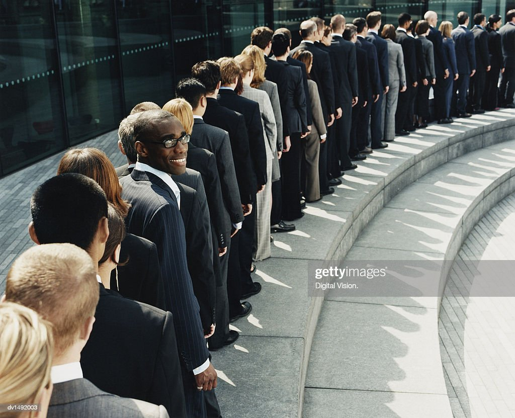 Businessman Standing Out in a Line of Business People Waiting Outdoors on a Step : Stock Photo