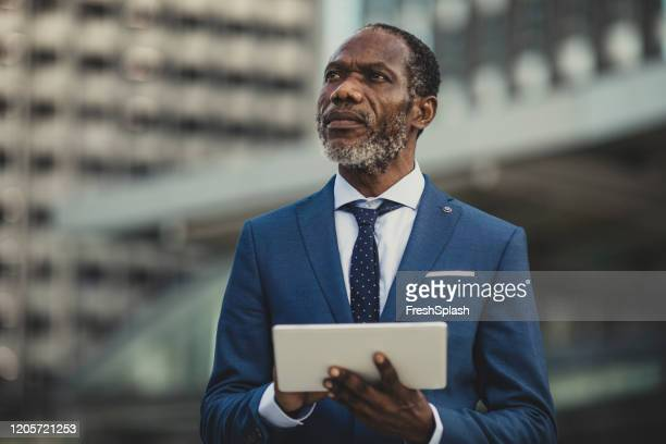 businessman standing outdoors and using digital tablet - economist stock pictures, royalty-free photos & images