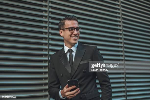 empresário em pé ao ar livre e usando telefone celular - estereótipo de classe alta - fotografias e filmes do acervo