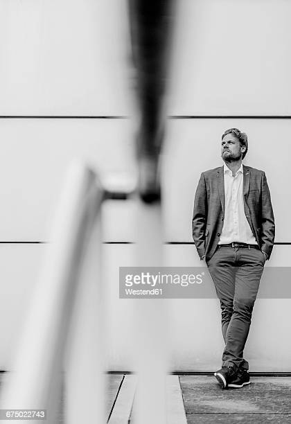 Businessman standing outdoors at a wall