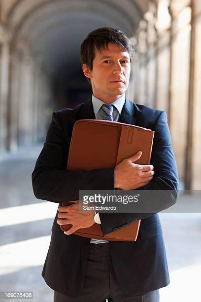 geschäftsmann holding aktentasche stehen im freien - bogen architektonisches detail stock-fotos und bilder
