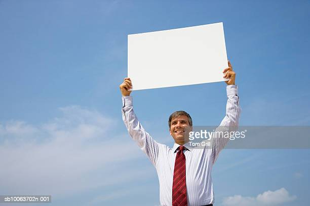 businessman standing outdoors, holding up blank sign - holding aloft stock pictures, royalty-free photos & images