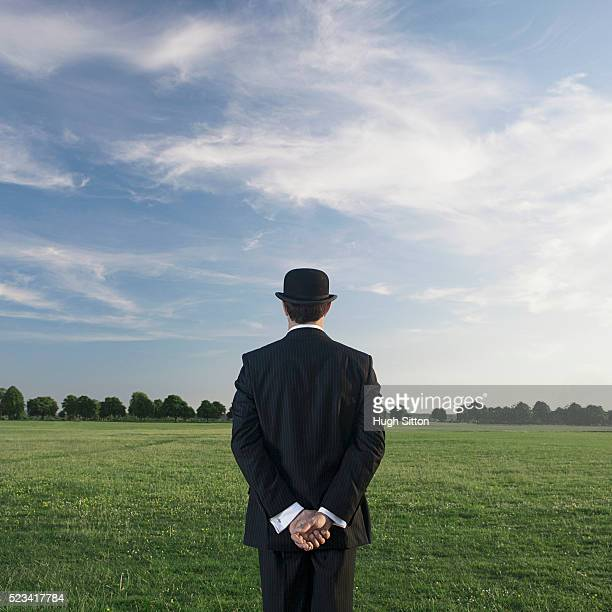 Businessman standing outdoors, wearing suit and bowler ha