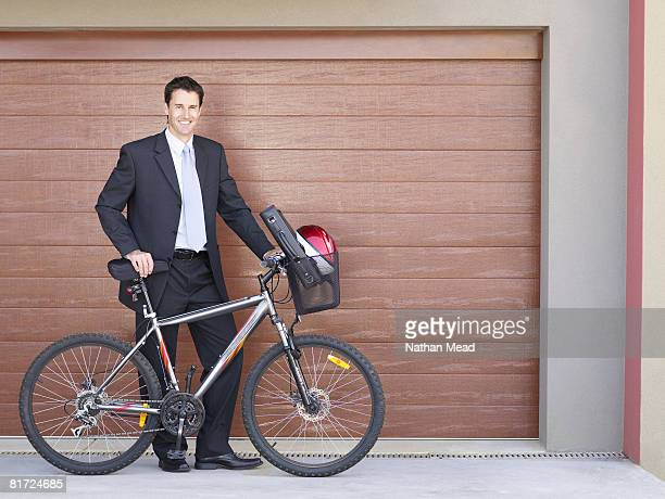 Businessman standing outdoors with bicycle smiling
