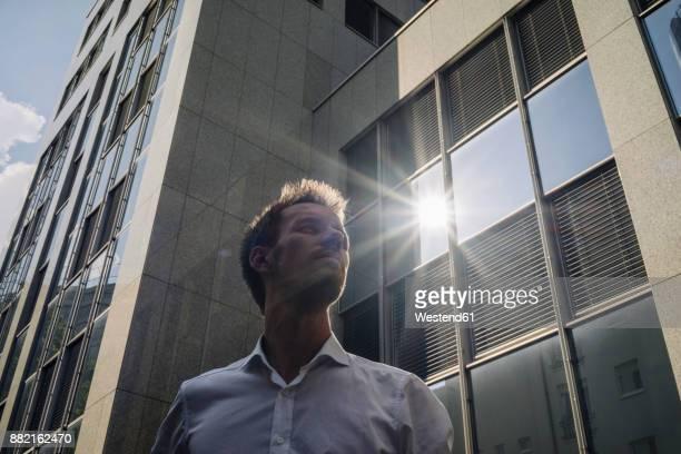 businessman standing outdoors with sun reflecting in office building - blickwinkel der aufnahme stock-fotos und bilder