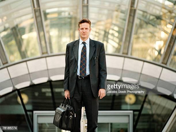 businessman standing outside a building - bogen architektonisches detail stock-fotos und bilder