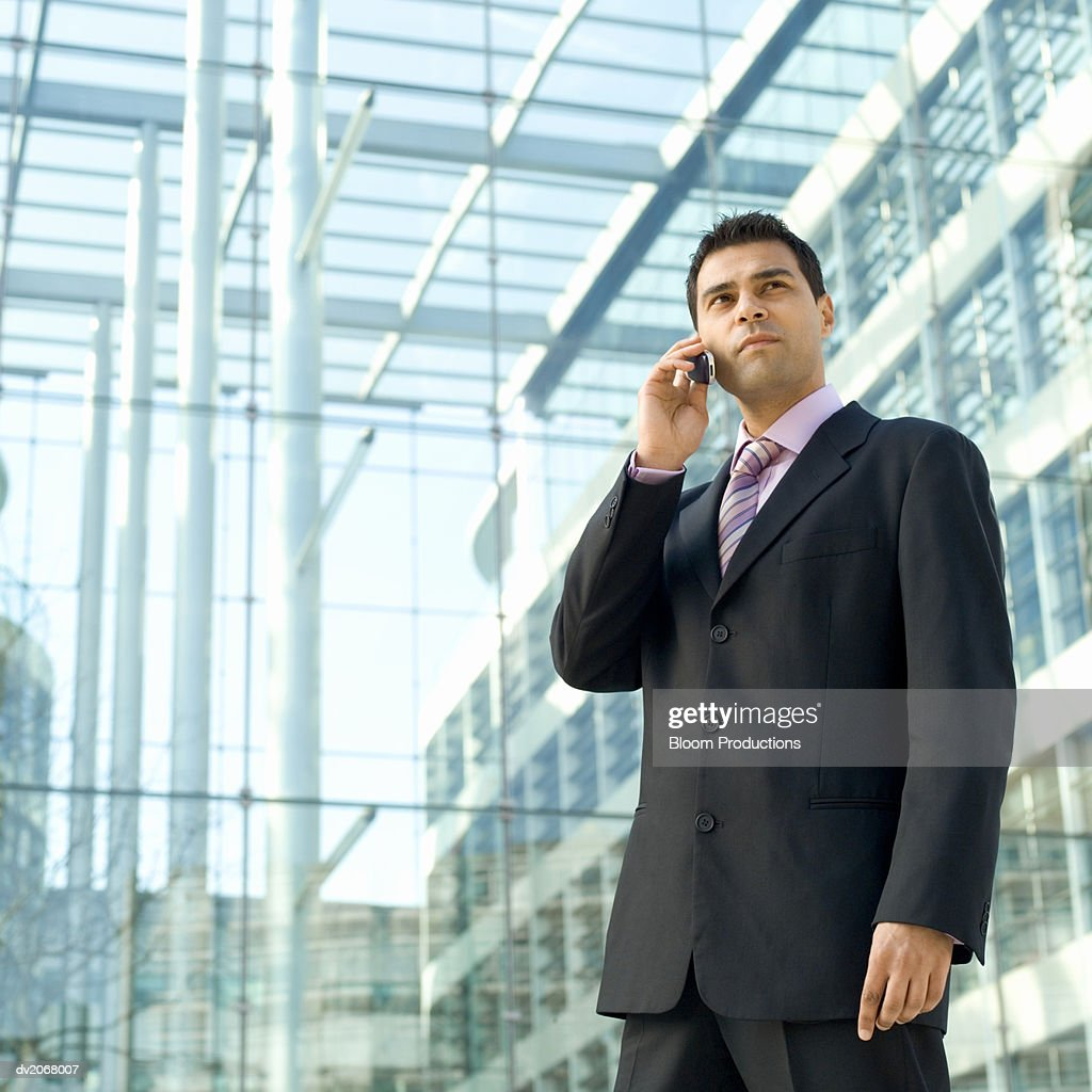 Businessman Standing Outside a Glass Building, Talking on His Mobile Phone : Stock Photo